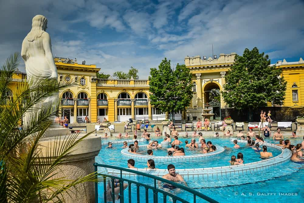 image of the outside pool with people swimming at the Szechenyi Baths in Budapest